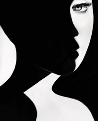 High contrast black and white portrait of a beautiful girl. Girl's face with shadow. Good and evil concept. Fine art concept. Fashion portrait. Dark side person. Good and bad concept. beauty portrait
