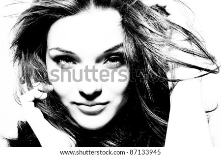 High contrast black and white portrait of beautiful girl with fluttering hair.
