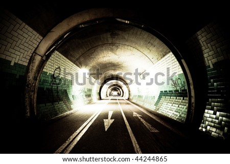 High-contrast exposure of a tunnel with arrows on the street
