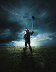 High contrast image of a scary clown with a floating balloon on a field