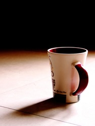 High contrast image of a white maroon tall isolated ceramic henley mug placed on a white blown out surface with sunlight casting a shadow and the bright foreground fading into dark background