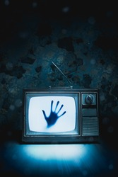 High contrast image of an old vintage TV with a hand inside