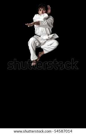 High Contrast karate young male fighter jumping on black background.
