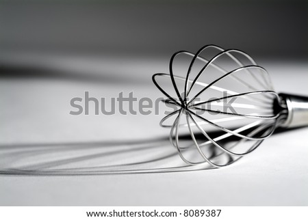 High contrast view of a standard whisk revealing interesting shadows. - stock photo