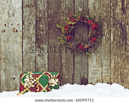 High contrast vintage image of a home made christmas wreath with natural decorations hanging on a rustic wooden wall and two gifts in the snow.