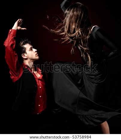 High contrast Young couple passion flamenco dancing on red light background.