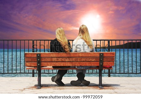 High definition image of two young ladies sitting on bench at the edge of a lake watching a colorful sunset.