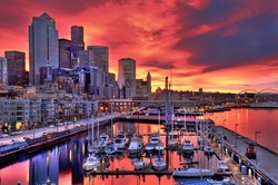 High dynamic image of Seattle skyline in dramatic sunrise colors across pier-66 waterfront