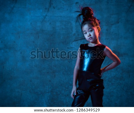 High Fashion asian model girl in colorful bright neon uv blue and purple lights colorful make up. Looks at you. Glitter Vivid neon light
