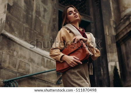 High Fashion Clothing. Beautiful Sexy Woman Wearing Fashionable Spring Or Fall Clothes ( Shirt, Scarf, Pants, Sweater, Leather Bag ) Outdoors. Female Model In Stylish Elegant Outfit Posing In Street