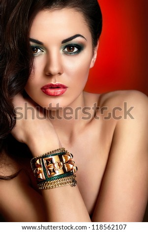 High fashion look.glamor closeup portrait of beautiful sexy Caucasian young woman model with red lips,bright green makeup, with perfect clean skin with jewelery on hand isolated on red background