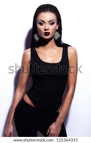 High fashion look.glamor portrait of beautiful sexy stylish brunette Caucasian young woman model with black lips,bright makeup, with perfect clean wet skin in black cloth