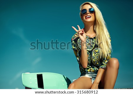 Stock Photo High fashion look.glamor stylish sexy beautiful young blond  model girl in summer bright casual hipster clothes with skateboard behind blue sky