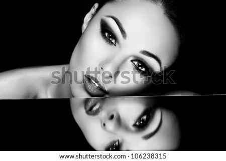 High fashion look.glamour fashion portrait of beautiful sexy brunette girl with bright makeup and her reflection in mirror table on dark