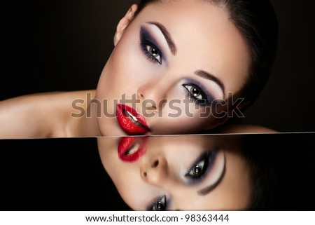 High fashion look.glamour fashion portrait of beautiful sexy brunette girl with bright makeup and red lips and her reflection in mirror table on dark