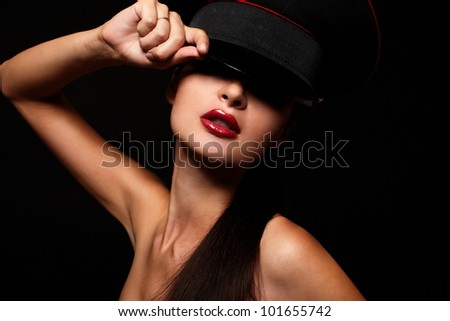 High fashion look.glamour portrait of beautiful sexy young female woman with red lips on black background with hat