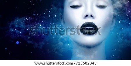 Stock Photo High Fashion Model Girl Portrait with Trendy gothic Black Make up, dark space background with clouds and stars. Halloween Vampire fantasy Woman portrait with black matte lips  deep blue background.