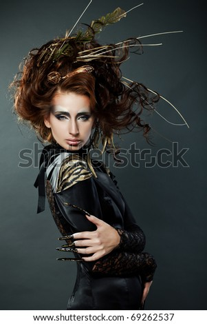 High fashion model in black dress, with long nails and creative hairstyling on grey background