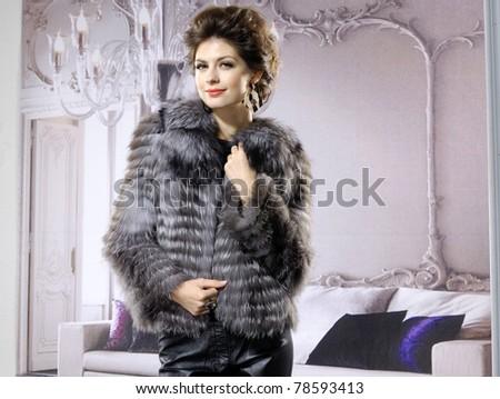 High fashion model in fur coat wearing posing