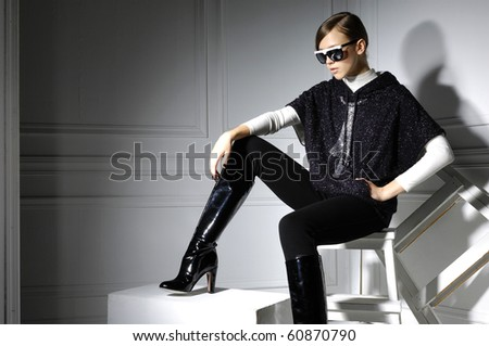 High fashion model in modern dress sitting in the studio