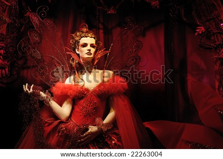 High fashion model in red dress at a fantasy party - stock photo
