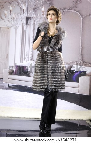 High fashion model in winter fur coat clothes posing in the studio