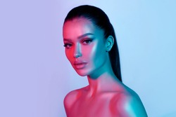 High fashion model metal silver lips and face woman in colorful bright neon UV blue and purple lights, posing in studio, beautiful girl, glowing makeup, colorful makeup. Glitter Bright Neon Makeup