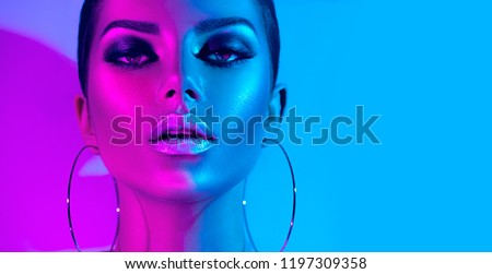 High Fashion model metallic silver lips and face woman in colorful bright neon uv blue and purple lights, posing in studio, beautiful girl, glowing make-up, colorful make up. Glitter Vivid neon makeup #1197309358