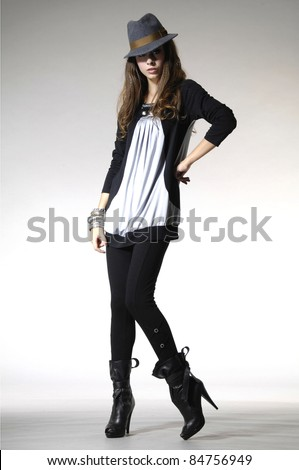High fashion model posing in hat posing in light background - stock photo