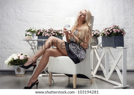 High fashion model sitting posing holding tea cup