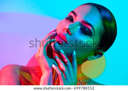 High Fashion model woman in colorful bright lights posing in studio, portrait of beautiful sexy girl with trendy make-up and manicure. Art design, colorful make up. Over colourful vivid background. - Shutterstock ID 699788152