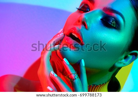 High Fashion model woman in colorful bright lights posing in studio, portrait of beautiful sexy girl with trendy make-up and manicure. Art design, colorful make up. Over colourful vivid background. - Shutterstock ID 699788173