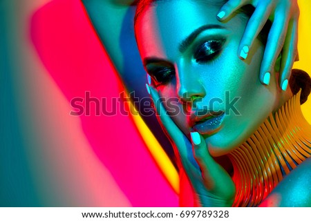 Stock Photo High Fashion model woman in colorful bright lights posing in studio, portrait of beautiful sexy girl with trendy make-up and manicure. Art design, colorful make up. Over colourful vivid background.