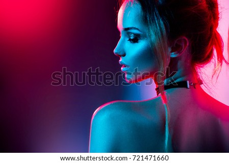 Stock Photo High Fashion model woman in colorful bright lights posing, portrait of beautiful  girl with trendy make-up. Art design, colorful make up. Over colourful vivid background.