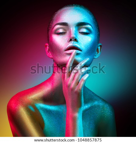 High Fashion model woman in colorful bright sparkles and neon lights posing in studio, portrait of beautiful sexy girl, trendy glowing make-up. Art design colorful make up. Glitter Vivid makeup