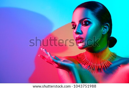 High Fashion model woman portrait in colorful bright neon lights, beautiful party girl with trendy make-up, manicure, haircut. Pointing hand, advertising gesture over colourful vivid background