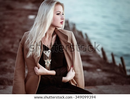 High fashion photo of elegant woman in black long dress, coat and stylish necklace in boho style.