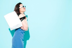 High fashion portrait of young beautiful brunette woman wearing nice blue summer dress.Sexy trendy model posing near blue wall in studio.Fashionable female in sunglasses. Holding shopping bag