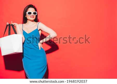 High fashion portrait of young beautiful brunette woman wearing nice blue summer dress.Sexy trendy model posing near red wall in studio.Fashionable female in sunglasses. Holding shopping bag