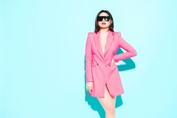 High fashion portrait of young beautiful brunette woman wearing nice pink summer suit.Sexy trendy model posing near blue wall in studio.Fashionable female in sunglasses