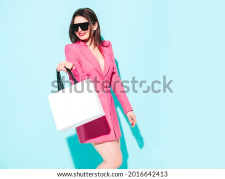 High fashion portrait of young beautiful brunette woman wearing nice pink summer suit.Sexy trendy model posing near blue wall in studio.Fashionable female in sunglasses. Holding shopping bag.Walking