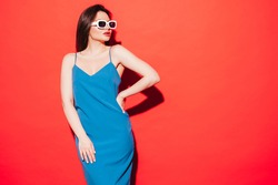 High fashion portrait of young beautiful brunette woman wearing nice summer blue dress.Sexy trendy model posing near red wall in studio.Fashionable female looking at camera in sunglasses. Red lips