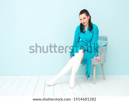 High fashion portrait of young beautiful brunette woman wearing nice trendy summer dress.Sexy fashion model posing near light blue wall in studio.Fashionable female sitting in chair