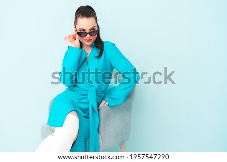 High fashion portrait of young beautiful brunette woman wearing nice trendy summer dress.Sexy fashion model posing near light blue wall in studio.Fashionable female indoors in sunglasses