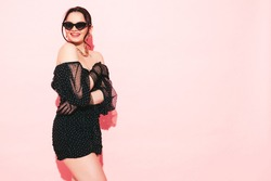 High fashion portrait of young beautiful brunette woman wearing nice trendy summer polka-dot dress and gloves.Sexy fashion model posing near light pink wall in studio.Fashionable female in sunglasses