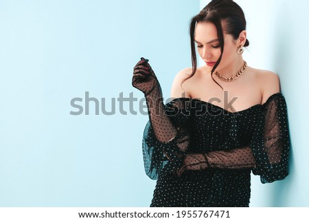 High fashion portrait of young beautiful brunette woman wearing nice trendy summer polka-dot dress and gloves.Sexy fashion model posing near light blue wall in studio.Fashionable female