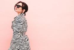 High fashion portrait of young beautiful brunette woman wearing nice trendy summer zebra coat.Sexy fashion model posing near pink wall in studio.Fashionable female in sunglasses