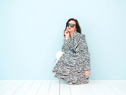 High fashion portrait of young beautiful brunette woman wearing nice trendy summer zebra coat.Sexy fashion model posing near light blue wall in studio.Fashionable female indoors in sunglasses
