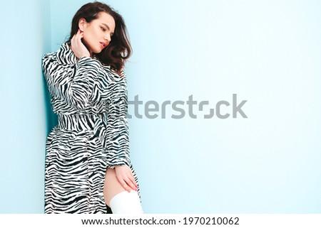 High fashion portrait of young beautiful brunette woman wearing nice trendy summer zebra coat.Sexy fashion model posing near light blue wall in studio.Fashionable female indoors