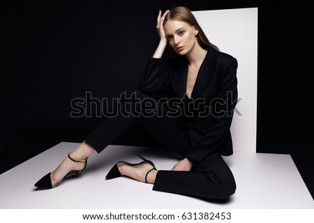 High fashion portrait of young elegant woman in black suit. Studio shot.